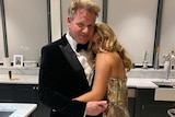 Gordon Ramsay dressed in a tuxedo, hugs is daughter Tilly who is wearing a gold dress.