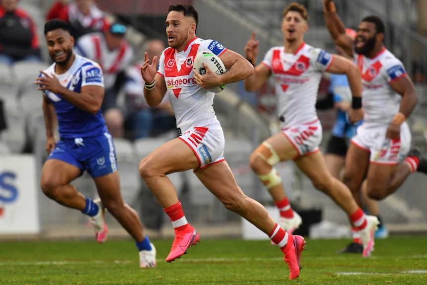 An NRL player carries the ball, sprinting away from a defender, as his teammates cheer behind him.