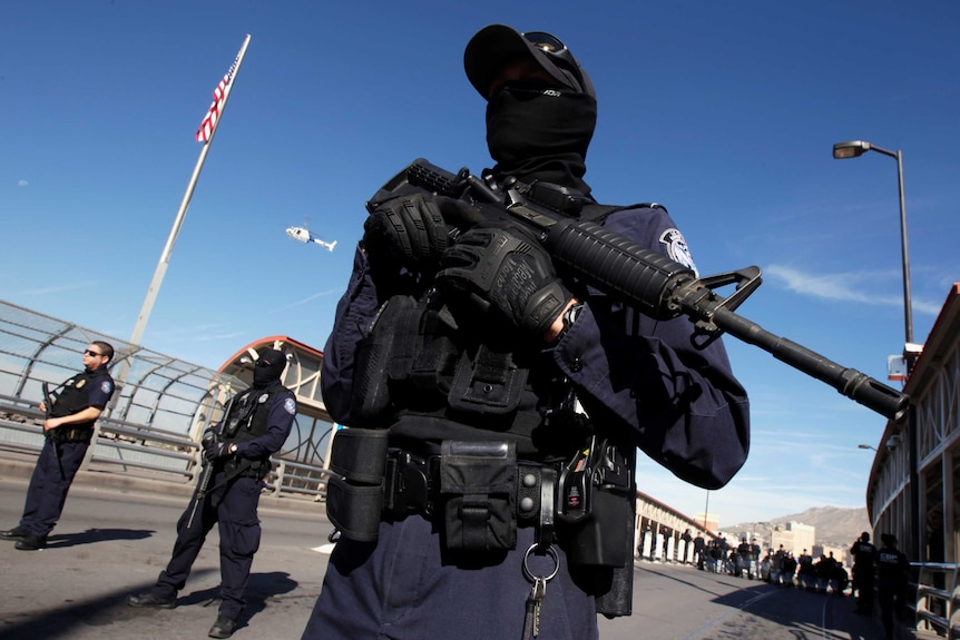 Masked border agents with guns on a training drill.