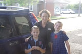 Two kids in thir school uniform in front of a car with a lady.