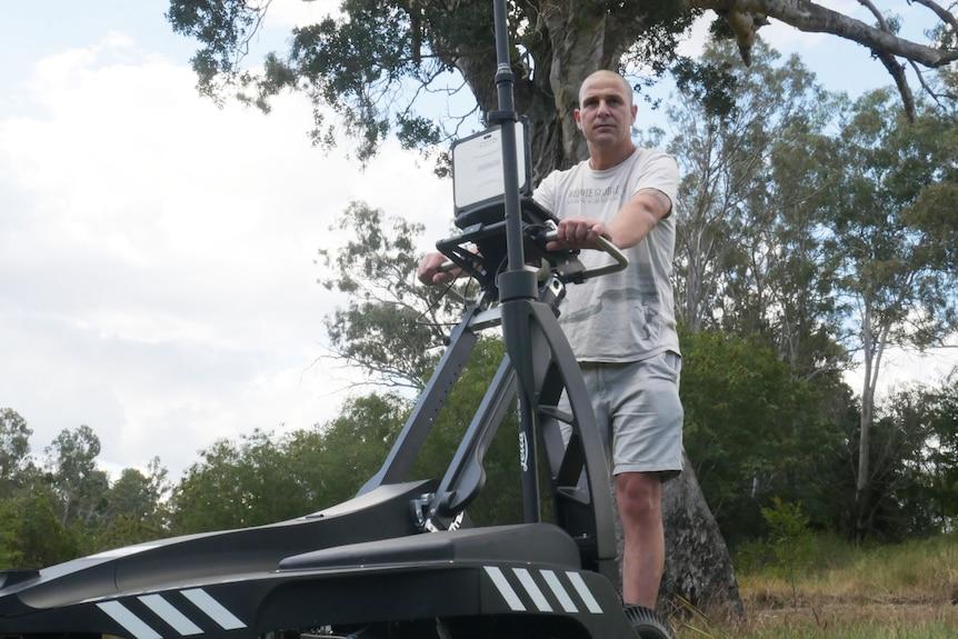 Daniel Thompson stands behind a Ground Penetrating Radar (GPR) scanner at Shapcott Park in Ipswich, west of Brisbane.