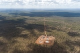 An aerial view of an exploration well in the Northern Territory's Beetaloo Basin on a patch of cleared land surrounded by bush