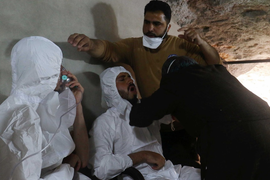 A man attended by rescue workers breathes through an oxygen mask