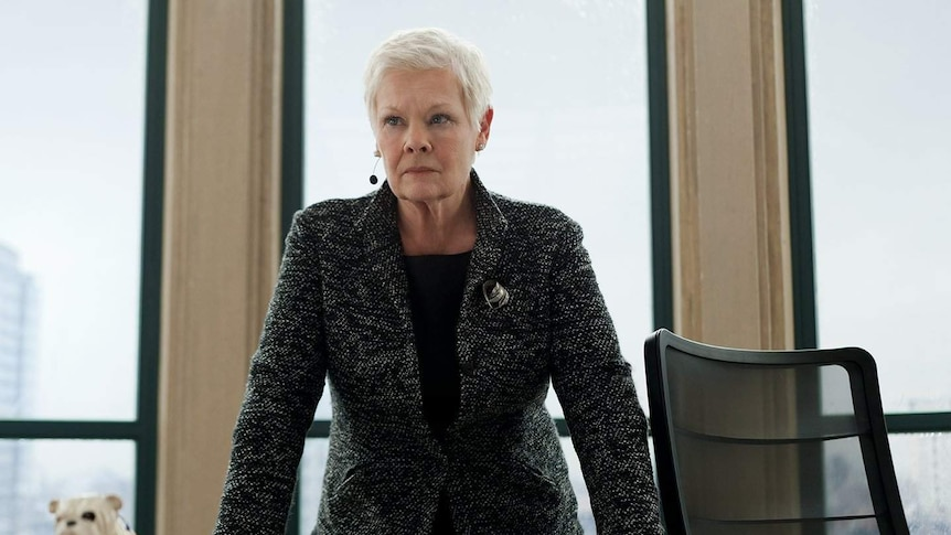 A woman leans on an office desk with a serious expression.