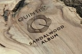 A sandwood branch has been sawn in half, with the polished side embossed with the Quintis logo, a series of rings.