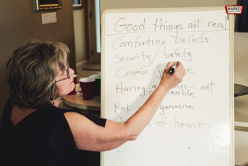 A woman stands at a whiteboard