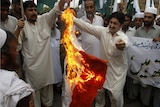 Pakistani protesters burn a representation of an Indian flag in Peshawar.