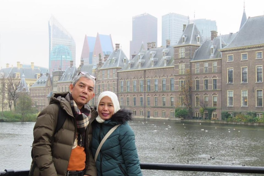 A couple standing with a building next to a river as background