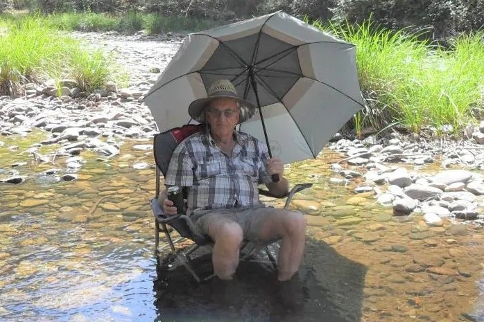Russell Hill sits on a camp chair that is in a low creek, holding an umbrella over him, with a beer in one hand.