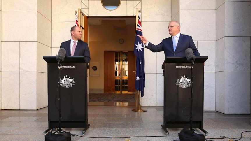 PM Scott Morrison points towards Treasurer Josh Frydenberg at a press conference