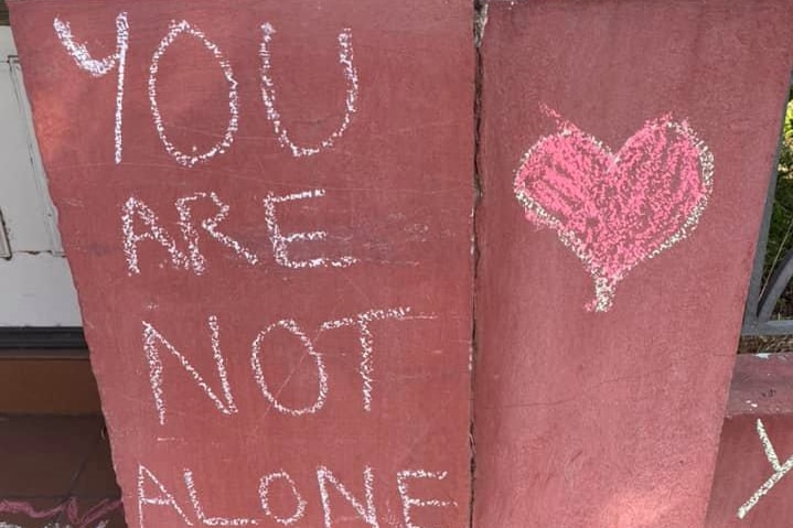 You are not alone with a red heart written in chalk on a wall.