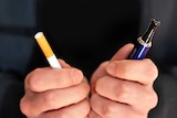 A person holds a tobacco cigarette in one hand and an electronic cigarette in the other.