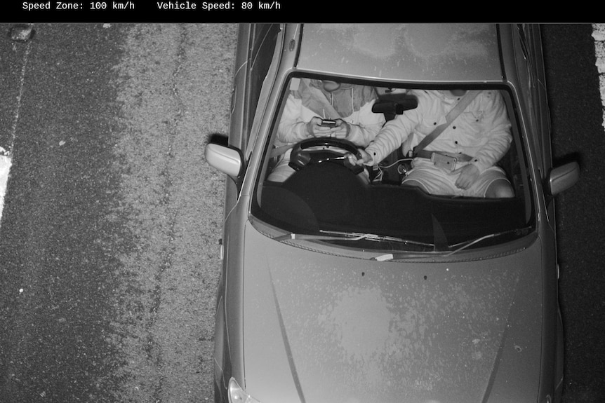 A driver used two hands to operate his mobile phone while his passenger steers