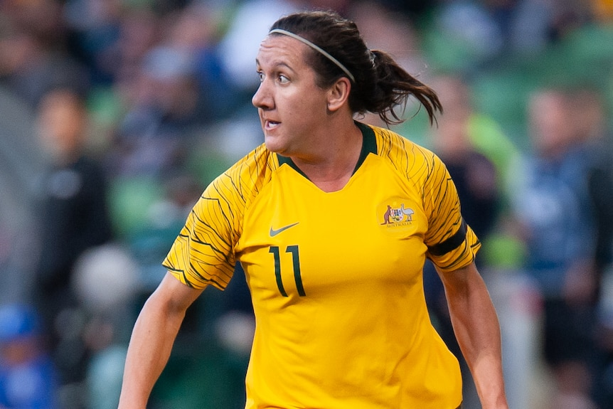 A female Australia football international looks to her right during a match against Argentina.