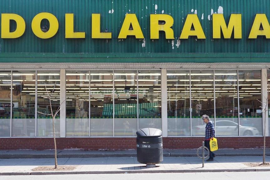 A scruffy man with a plastic bag walks past a bargain shop
