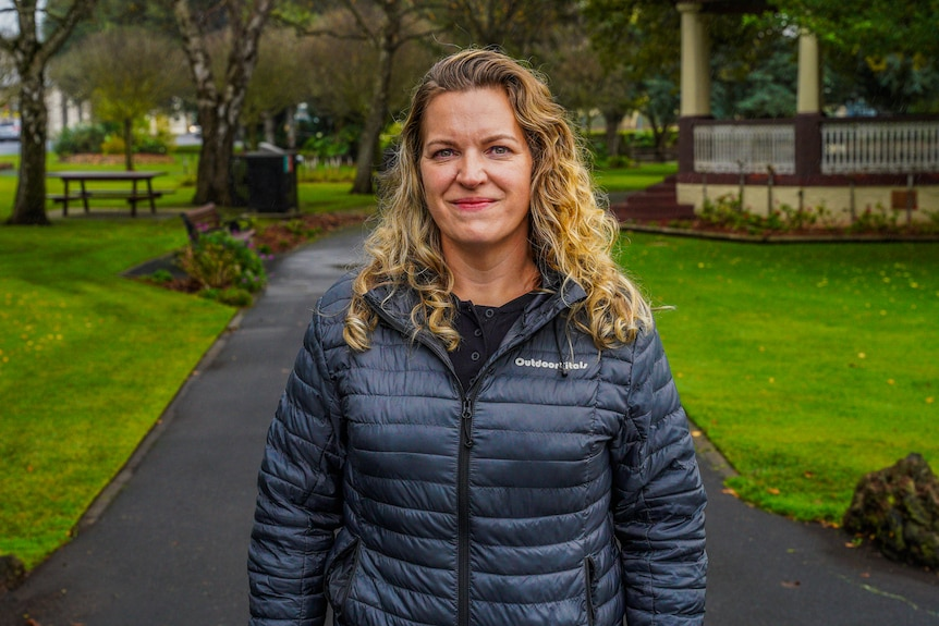 A woman in a black puffer jacket smiles for a photo in a park.