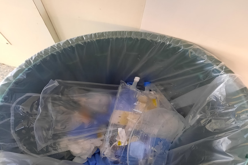 a plastic bin with iv drips and plastic gowns in it
