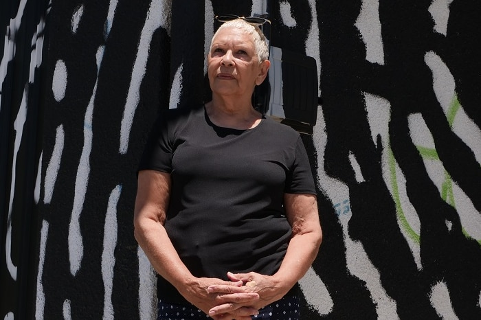 Indigenous woman and artist Glennys Briggs stands in front of two-storey building on a sunny day.