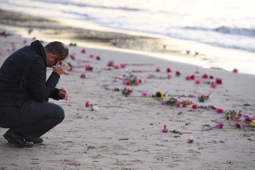 A man crouches by the waters' edge holding his head in his hands.