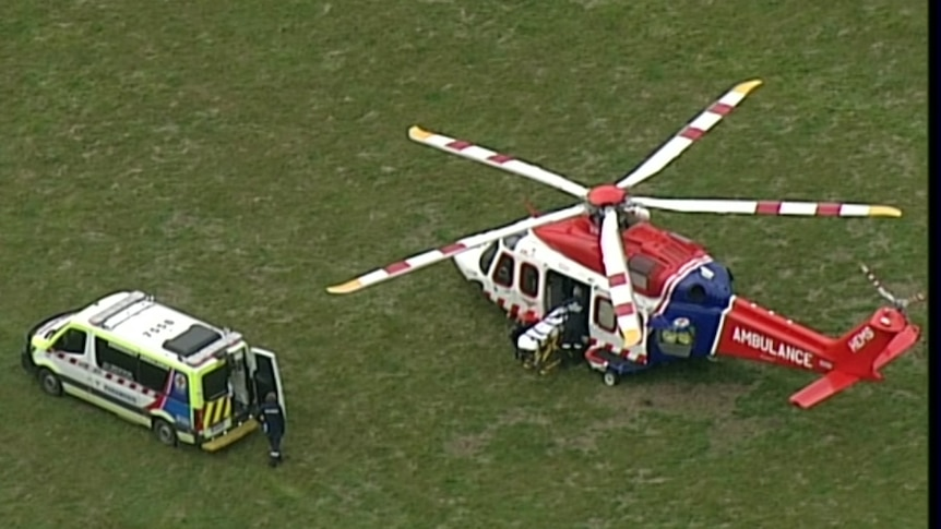 An ambulance chopper and and an ambulance in the middle of a green field.