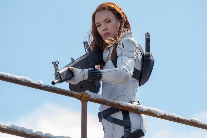 Scarlett Johansson in a white superhero suit points a gun downwards, over a fence