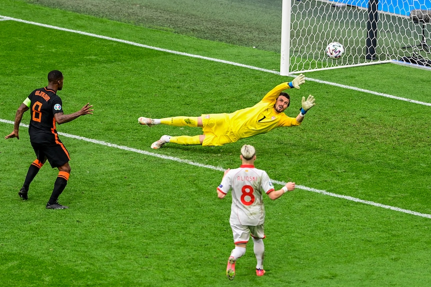 A Dutch player stands and watches his shot hit the net as the grounded goalkeeper raises his arms during a Euro 2020 match.