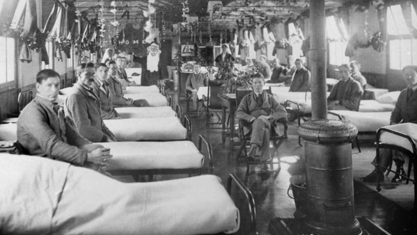 Soldiers lined up beside their beds in military hospital