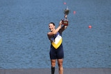 A smiling rower holds a trophy up high
