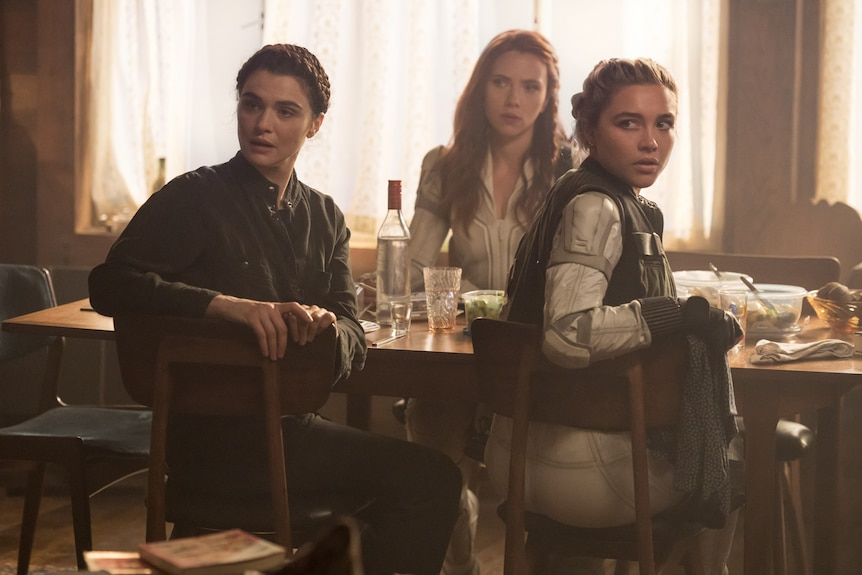 Three women sit at dinner table, turning towards camera as if looking at someone.