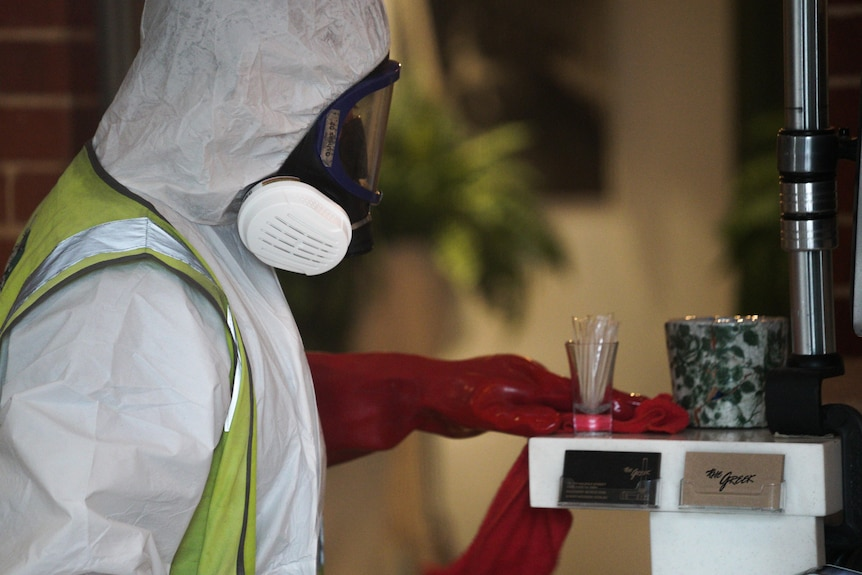 A cleaner wearing personal protective equipment.