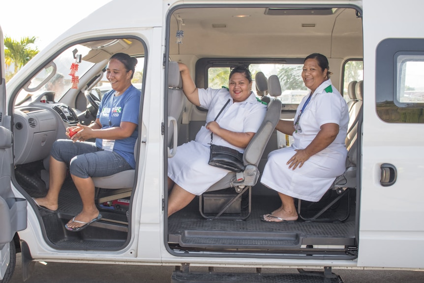 Three woman smile out of a white van with doors open.