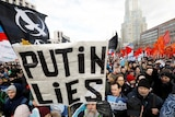Protesters hold up signs, including one which reads 'Putin lies'