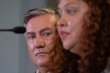 Eddie McGuire looks out from behind Jodie Sizer as she speaks at a press conference