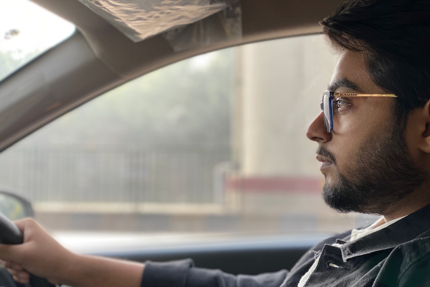Man looking at the road while driving a car, experiencing some nervousness and fear.