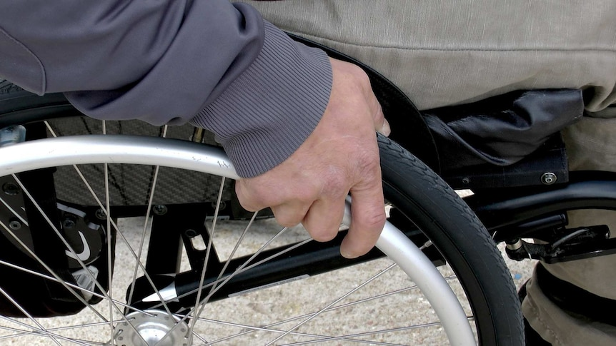 A man's hand on the wheel of a wheelchair