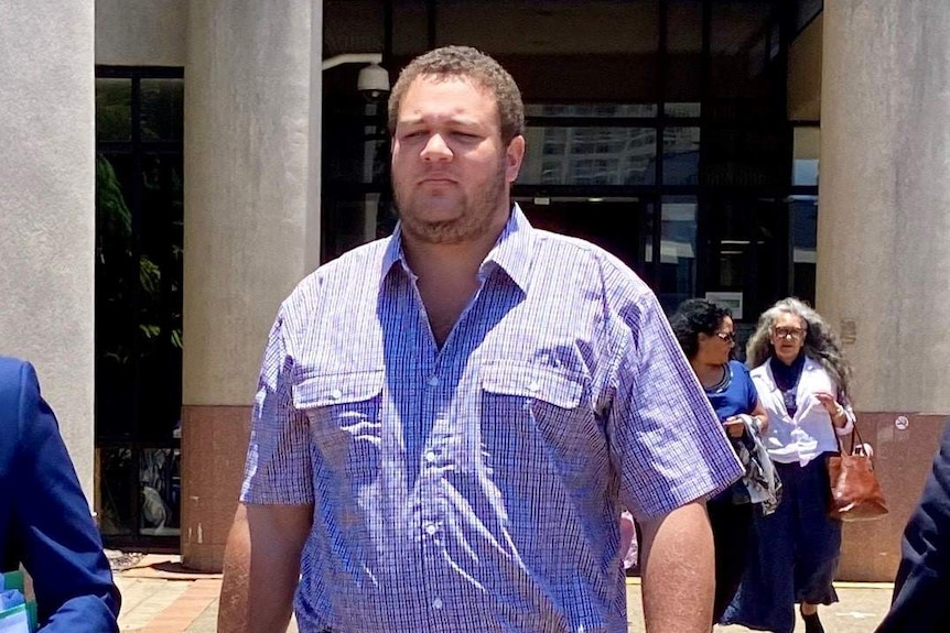 A heavyset man with close-cropped, curly hair and beard stubble walks away from a court building.