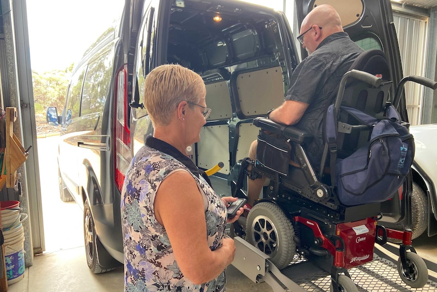 A man in a wheelchair on a lifter at the back of a van with a woman standing nearby