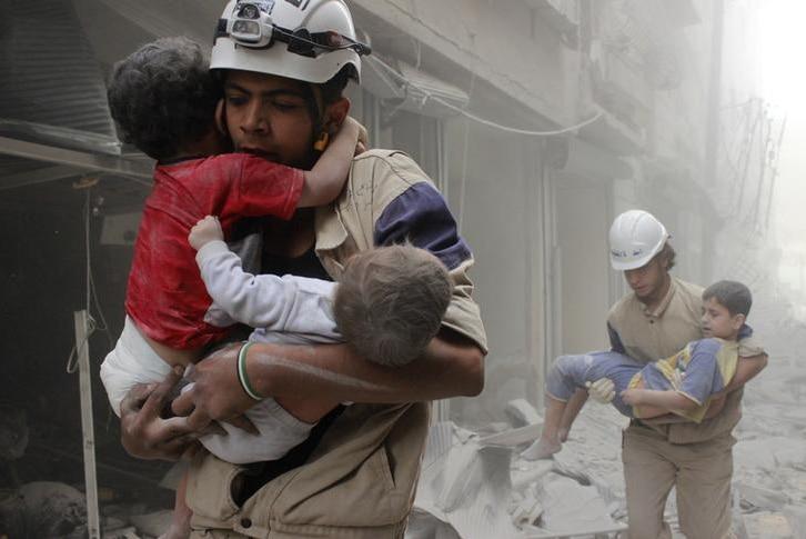 White Helmet volunteers in Syria carry children