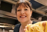Woman wearing black Bella T-shirt in a commercial kitchen holding up fresh tagliatelle pasta to the lens.