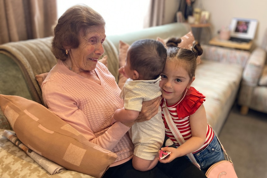 A woman smiles with a baby and a young girl on her lap.