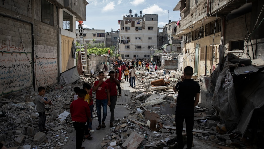 Palestinian children in foreground of photo walk amid the rubble of a house that was hit by Israeli airstrikes in Gaza City