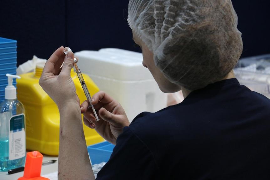 A woman prepares a pfizer vaccine shot in Perth