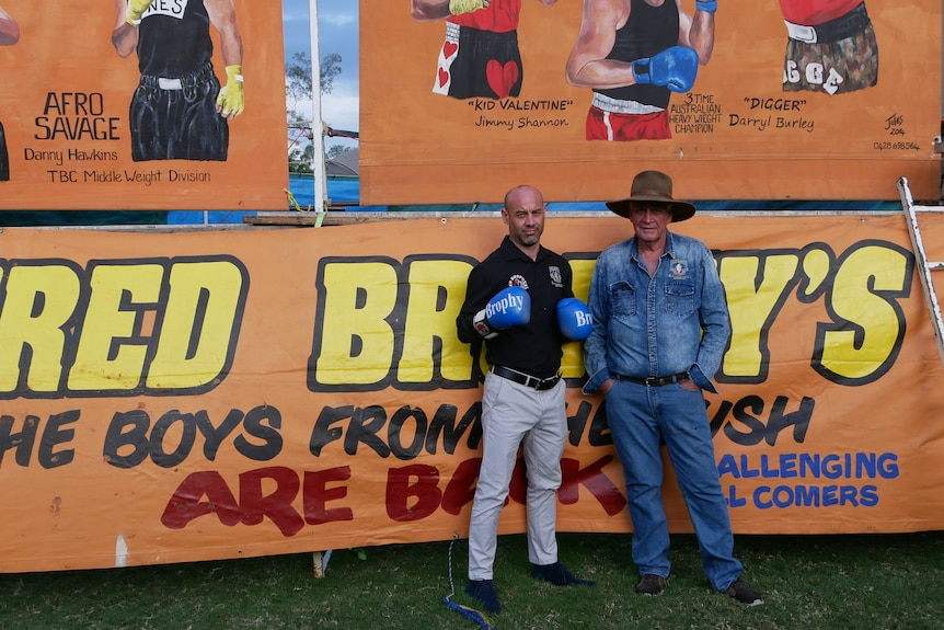 A man in black next to a man in blue out the front of an orange circus tent.