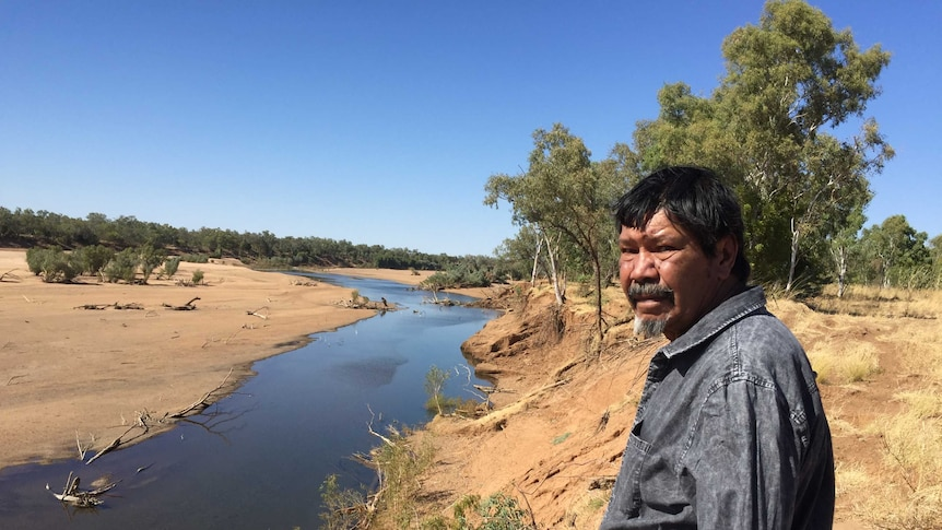 An Indigenous man inspects the site where dozens of remains were found.
