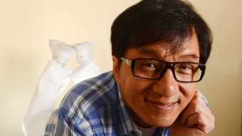 Jackie Chan wears glasses and smiles at the camera.