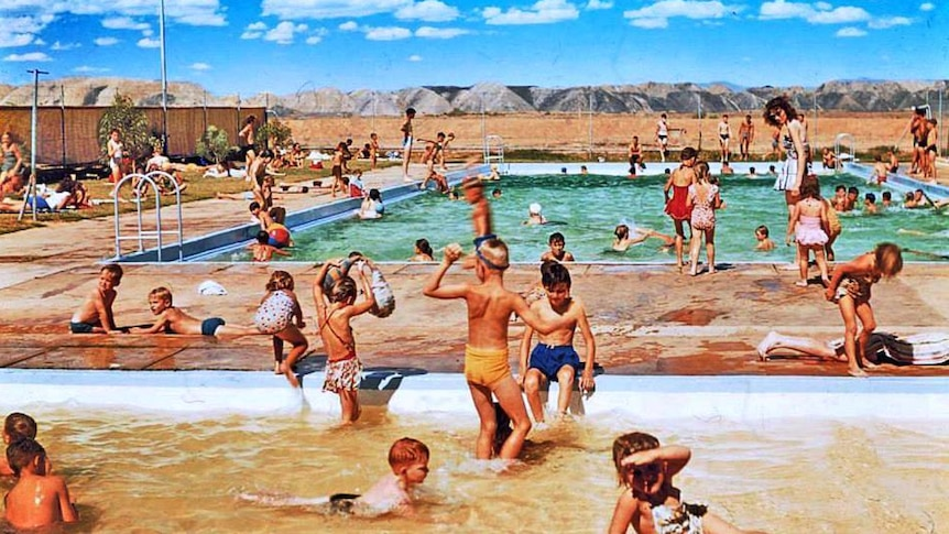 A large swimming pool filled with people with large hills in the background.