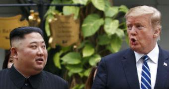 Kim Jong-un walks to the right of Donald Trump as they stroll through a hotel garden