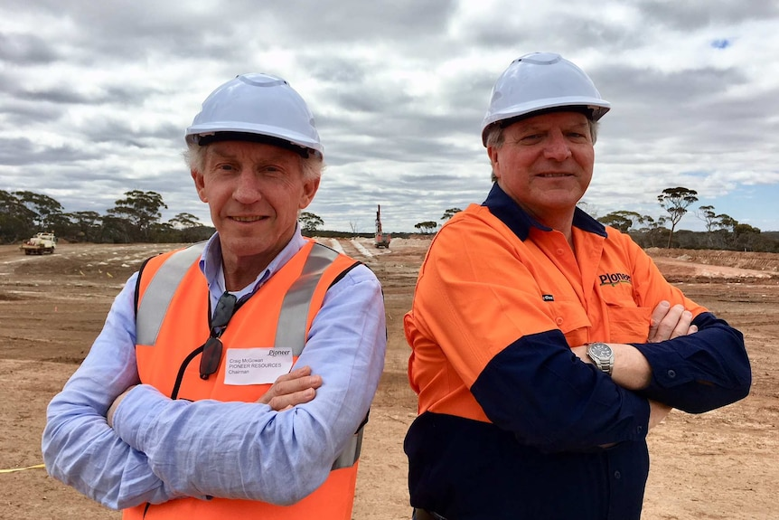 Two men in hard hats stand back to back on mine site