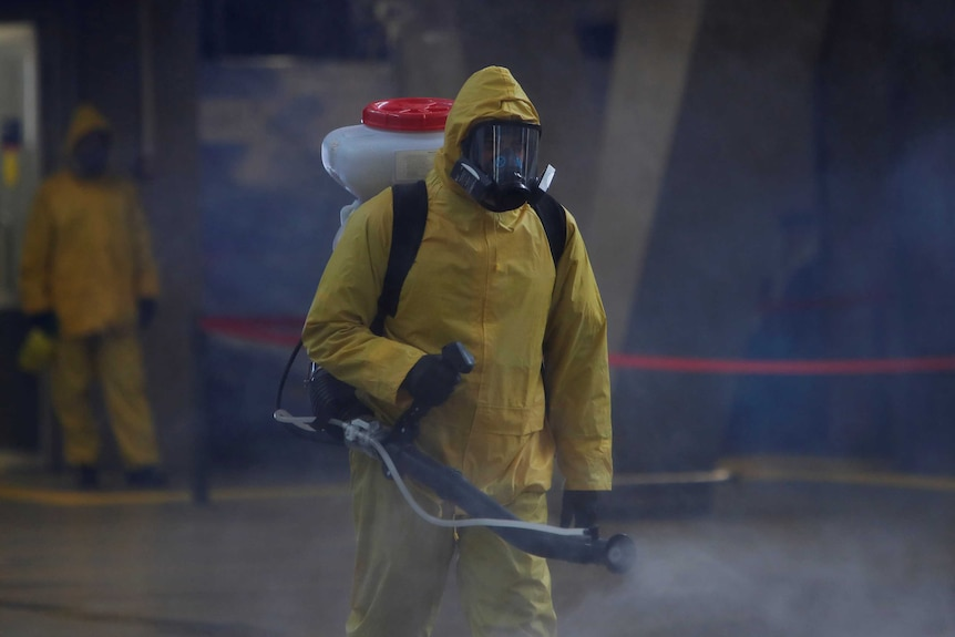 A figure in a yellow hazmat suit sprays disinfectant into the air.
