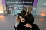 Relatives hug in front of the international arrivals sign at an airport